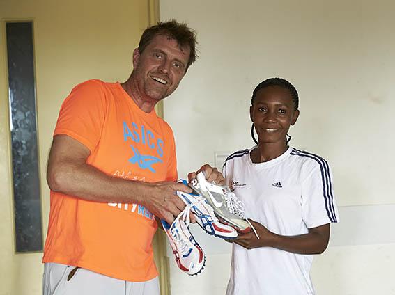 Tansanialainen juoksija Adelina Asimwe vastaanotti LiiKen toiminnanjohtajalta Ari Koivulta Nooralotta Nezirin vanhat kengät
